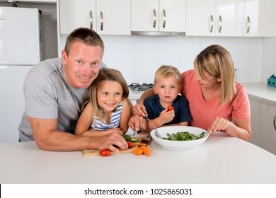 young attractive couple mother and father preparing salad together with little son and young beautiful daughter in healthy vegetable nutrition education and family lifestyle
