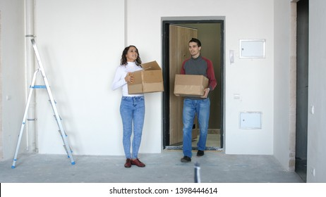 A young attractive couple moving into a new home. A couple is standing on the doorstep holding boxes in their hands.