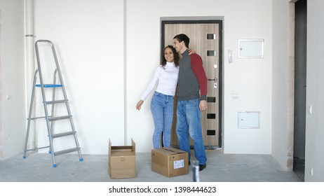A young attractive couple moving into a new home. A couple is standing on the doorstep next to boxes