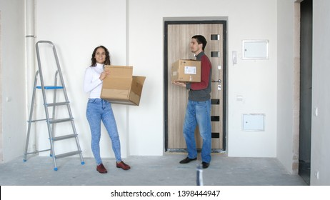 A young attractive couple moving into a new home. A couple is standing on the doorstep
