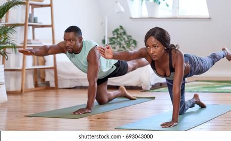 Junge attraktive Paare, die Yoga-Stretching-Training zu Hause, gesunde Lifestyle-Körperpflege