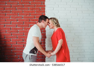 Young attractive couple: pregnant mother and happy father standing near contrast red and white brick wall