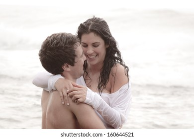 Young attractive couple sharing a happy moment at the beach