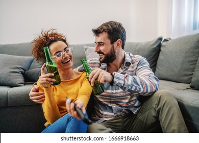 Young attractive couple sitting at home, drinking beer and watching television. Relaxation at sunday afternoon.