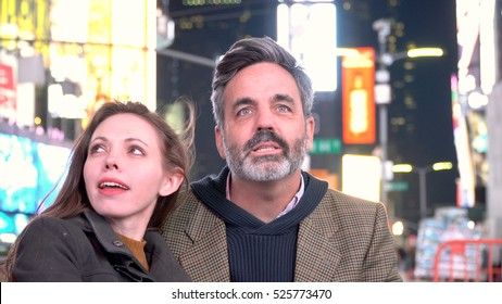 Young attractive couple sitting in Times Square New York City looking at the bright billboard neon signage in cold weather. Location for New Years Eve celebration when ball drops