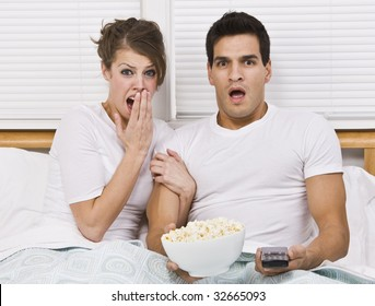 A young, attractive couple is sitting together in bed and watching TV.  They look shocked or scared, and are looking away from the camera.  Horizontally framed shot.
