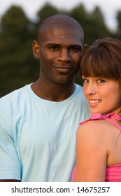 A young and attractive couple, smile while staring at the camera. - vertically framed