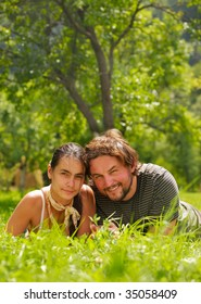 Young attractive couple smiling and lying on a grass