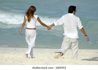 Young attractive couple walking along the beach holding hands