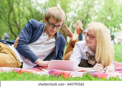 young attractive couple wearing glasses is working or studying with laptop book note and pen lying on blanket in green park at sunny summer day