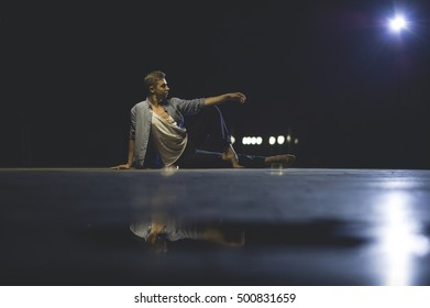 Young attractive dancer in casual cloth sitting on the street and posing. Modern choreography.