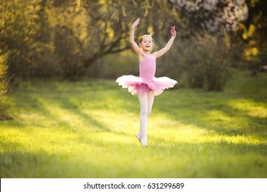 Young attractive dancer performer workout at the spring garden. 9 years girl dance in the magic evening sunlight in pink ballet dress. Active and healthy kid have fun outdoor in park