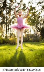 Young attractive dancer performer workout at the spring garden. Girl dance in the magic evening sunlight in pink dress. Fine art ballet concept. Surreal dancing. Jump to the future and new life start