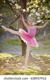 Young attractive dancer performer workout at the spring garden. Girl dance in the magic evening sunlight in pink ballet dress. Active healthy kid have fun outdoor in park under blooming magnolia tree