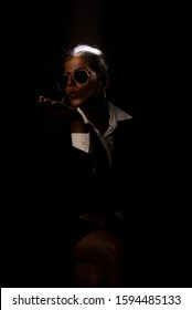 Young and attractive dark skinned Indian Bengali brunette woman in western jacket and skirt giving flying kiss while sitting under spotlight in black copy space background. Indian fashion photography.