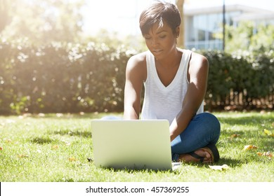 Young attractive dark-skinned college student wearing tank top and jeans sitting on the lawn at campus on sunny day, working on her thesis using laptop computer, looking busy and concentrated