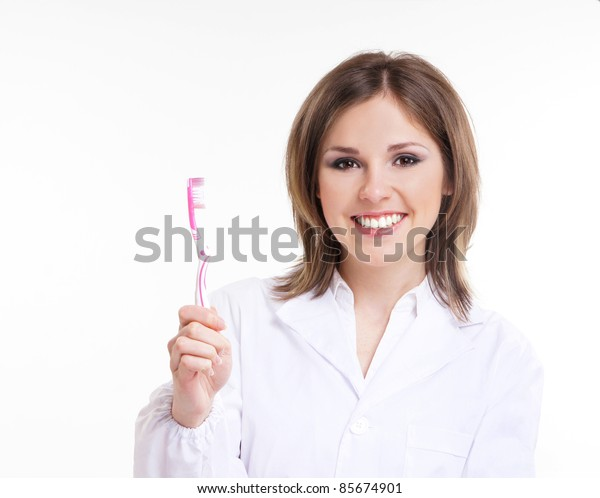 Young attractive dentist with a pink tooth brush isolated on white