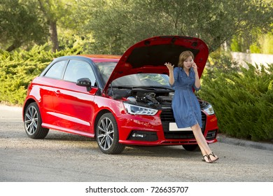 young attractive desperate and confused woman stranded on roadside with broken car engine failure crash accident calling on mobile phone for mechanic assistance in insurance company concept