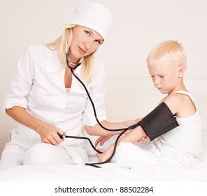 young attractive doctor examining an ill child and measuring his blood pressure  at home