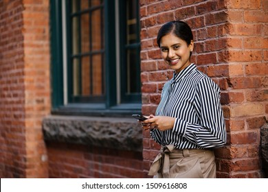 A young, attractive, dynamic and beautiful Indian Asian woman in a business casual outfit is texting on her smartphone as she leans against a red brick wall in a street in the city.