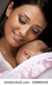 Young Attractive Ethnic Woman Holding Her Newborn Baby Under Dramatic Lighting.