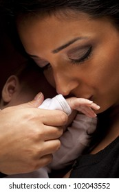 Young Attractive Ethnic Woman Kisses Her Newborn Baby Hand Under Dramatic Lighting.
