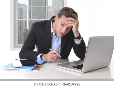 young attractive European businessman working in stress at office desk computer laptop suffering headache, worried and frustrated looking depressed and overwhelmed for too much work