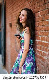 A young and attractive European Caucasian woman leans against a brick wall and is smiling as she uses her smartphone in the day as she waits for a friend. She is tall, slim and beautiful.