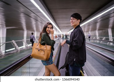 A young, attractive and excited diverse Asian interracial couple (Korean man and Indian woman) are smiling as they are going for a holiday. They are on an escalator in the airport to catch a flight.