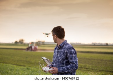 Young attractive farmer driving drone above field with tractor working in background