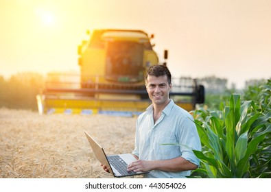 Young attractive farmer holding laptop and standing in corn field while combine harvesting wheat in background