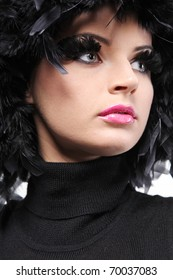 Young attractive fashion model with black feathers as hair.