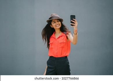 A young, attractive and fashionably dressed Indian Asian woman takes a selfie of herself against a plain grey background. She is smiling and wearing a fedora hat, orange shirt and black pants.