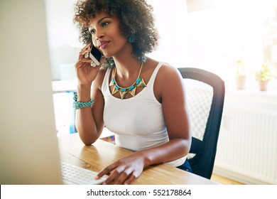 Young attractive female African American entrepreneur talking on a mobile phone as she sits at her desk in a high key bright home office