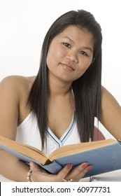 Young attractive female Asian student reading her school books