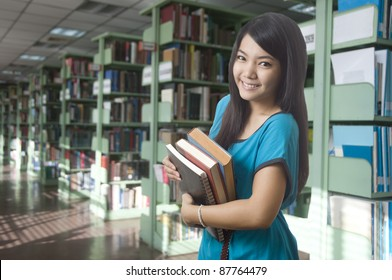 Young attractive female Asian student holding her school books in the library