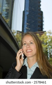 A young attractive female business professional is taking a call.