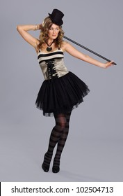 Young and attractive female circus artist over grey background