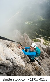 young attractive female climber on a steep and exposed rock face climbs a Via Ferrata in Alta Badia in the South Tyrol