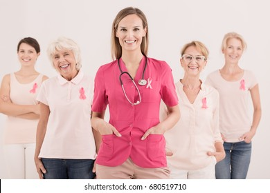 Young attractive female doctor with smiling women wearing pink