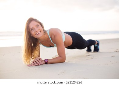 Young attractive female does planking exercise on the beach to strengthen her whole body.