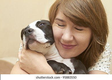 Young attractive female embracing her Pit Bull puppy