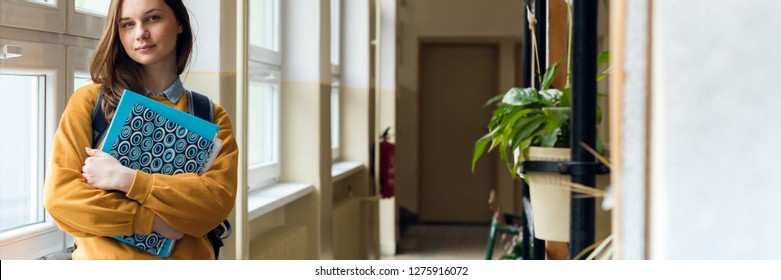 Young attractive female high school student standing by the window in the hallway at her school alone. Education concept.