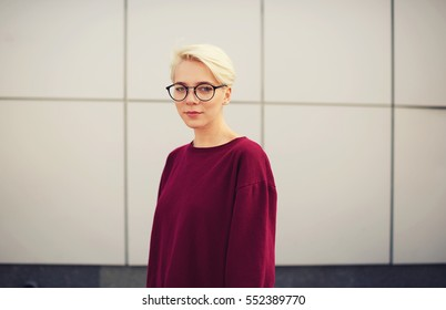 Young attractive female hipster student in eye glasses and trendy wool sweatshirt standing on urban settings wall background with copy space area for your advertising