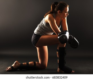 Young attractive female martial arts fighter.Resting after hard training.