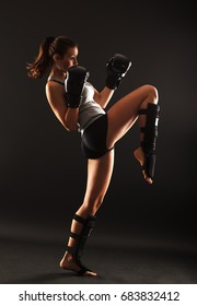 Young attractive female martial arts fighter.Knee kick.