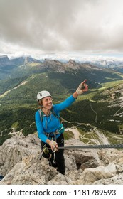 young attractive female mountain climber on a steep and exposed Via Ferrata in Alta Badia in the South Tyrol in the Italian Dolomites pointing to the summit and smiling