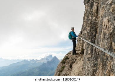 young attractive female mountain climber on an exposed Via Ferrata rock ledge in Alta Badia in the South Tyrol in the Italian Dolomites