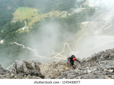 young attractive female mountain climber on a steep and exposed Via Ferrata in Alta Badia in the South Tyrol in the Italian Dolomites