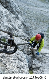 young attractive female mountain climber in the Dolomites of Italy climbing a Via Ferrata